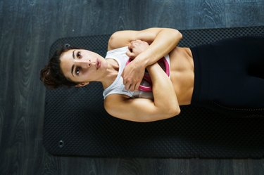 Young sportswoman on yoga mat doing situps in gym.