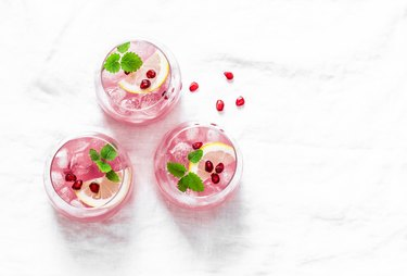 Pomegranate tequila cocktail. Summer light alcoholic drink,  cooling aperitif. On light background, top view, free space. Flat lay