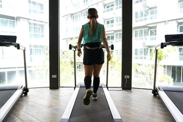 Asian woman walking on treadmill with bright buildings background