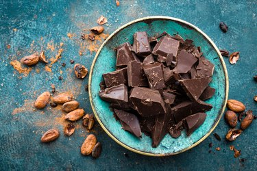 Dark chocolate chunks on a blue plate, with cacao scattered on the table