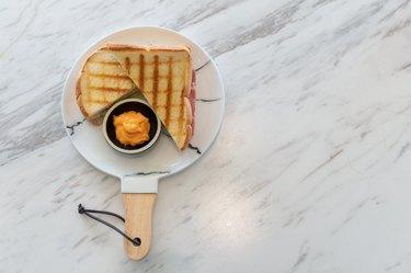 Ham cheese sandwich with custard sauce on marble