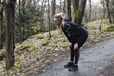 Full length of tired female athlete standing with hands on knees in forest