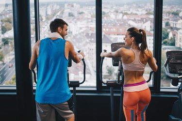 Back view of smiling athletic couple talking while exercising on cross trainer in a gym.
