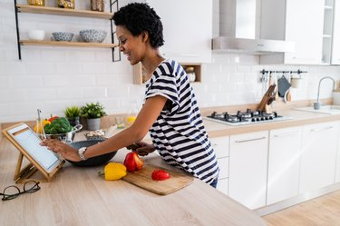 Young woman using a digital tablet while cooking