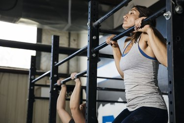 Women doing pull-ups at gym