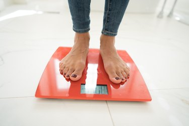 A woman's feet standing on a red scale in a white marble bathroom