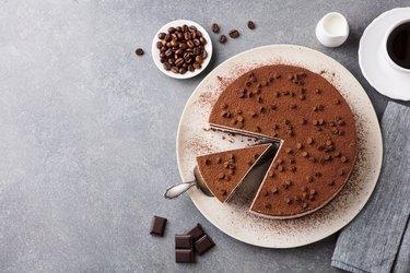 Tiramisu cake with chocolate decoration on a plate. Grey stone background. Top view. Copy space.