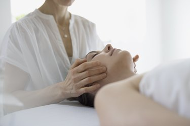 Serene woman receiving face massage on spa massage table