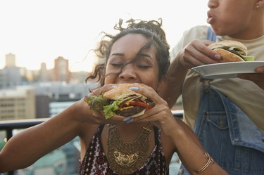 Rooftop BBQ with woman eating a burger