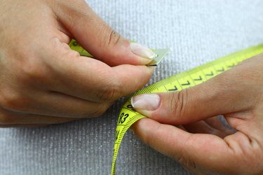 A close-up view of a woman measuring her waistline