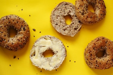 Closeup of a 12 grain bagel with butter on a yellow background