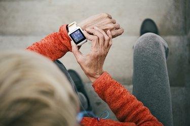 Senior woman checks her heart rate on smart watch taking a break