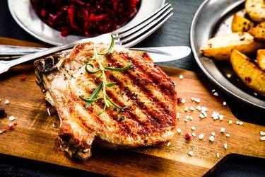 Oven bag baked pork chop and vegetables on wooden board