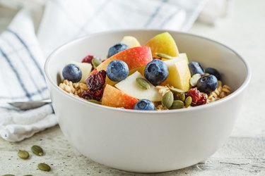 Bircher muesli or overnight oatmeal with apple, banana and blueberries in gray bowl.