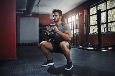 Man doing squats with a kettlebell in the gym