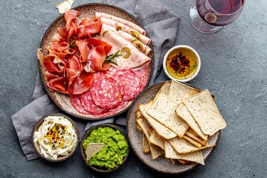 Antipasto. Meat platter, chips and sauces, red wine on gray background. Top view