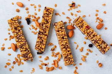 Cereal granola bar with nuts, fruits and berries on a whhite stone table. Granola bar. Healthy snack. Top view.
