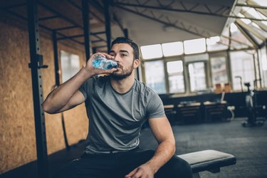 Man drinking water after training in gym