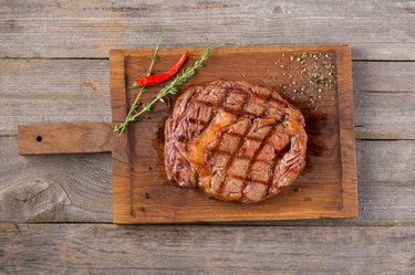Rib eye steak on wooden board, closeup