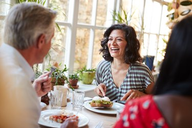 A happy woman eating breakfast with friends at a cafe