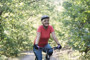 Older woman riding a mountain bike outdoors