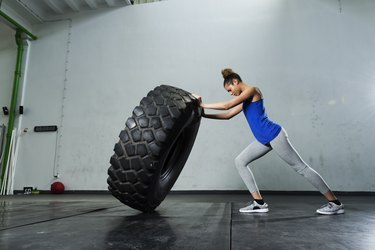 Young girl flipping tire at the gym to build muscles