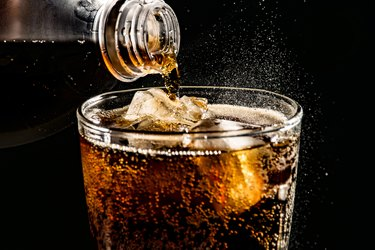 Close-Up Of Drink Pouring In Drinking Glass Against Black Background