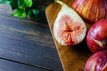 Fresh figs. Fruit with half isolated on wooden background.