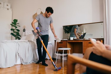 Full length of man cleaning bedroom with vacuum cleaner