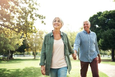 A healthy older couple walking together in a park