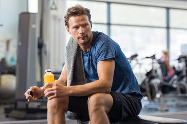 A man in the gym drinking a BCAA supplement drink after working out