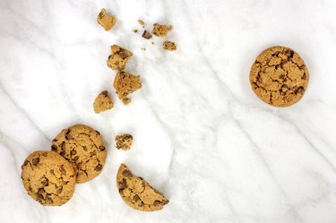 Chocolate chips cookies and crumbs on white marble
