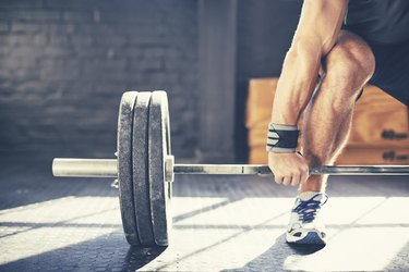 man deadlifting heavy barbell in gym, which could lead to hemorrhoids