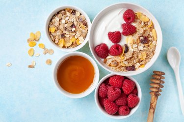 Greek yogurt in bowl with raspberries, honey and muesli on blue table top view.