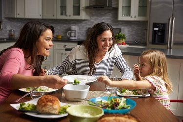 Female gay couple and daughter having dinner in their kitchen