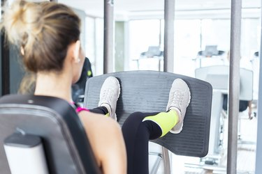 Female fitness instructor working out Leg press in health club