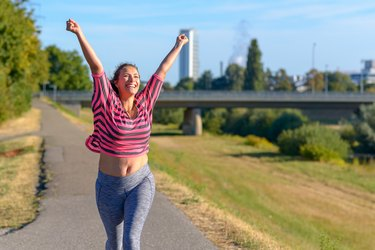 Happy fit woman cheering and celebrating after losing 100 pounds