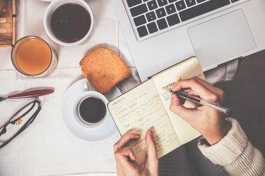 Having breakfast in early morning, writing in a food journal