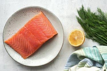 Fresh salmon steak, lemon and dill on concrete table.