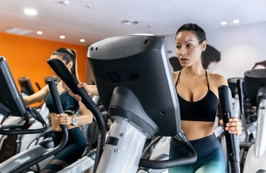 Two women working out in gym using an elliptical trainer