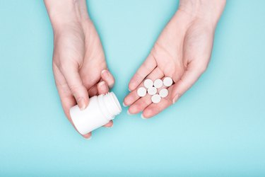 Close up of female hands holding pills
