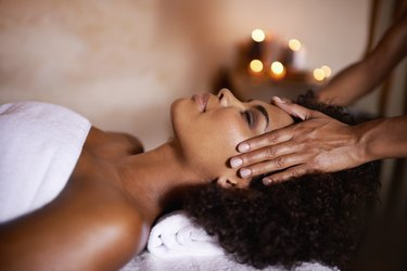 A woman in a white towel getting a head massage from a professional masseuse