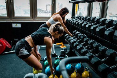 Two young women lifting weights in the gym