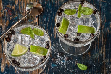 Directly Above Shot Of Juniper Berries And Lemon Slices In Gin and Tonic Glasses On Table