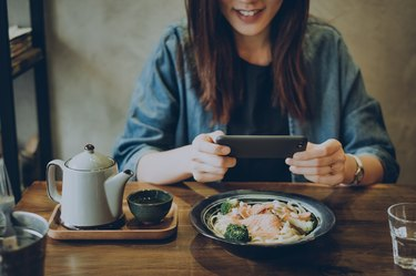 Smiling woman capturing her meal on table with smartphone in cafe