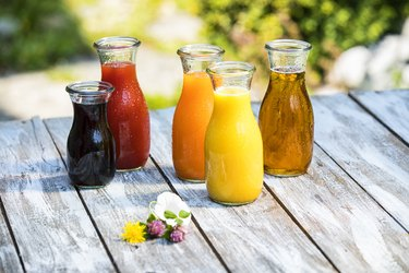 Glass bottles of various fruit juices