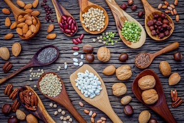 Various legumes and different kinds of nutshells in spoons. Waln