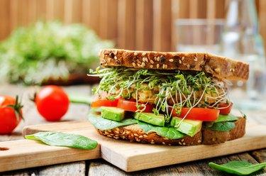 sprouts avocado tomato spinach chickpeas burger rye sandwich
