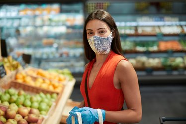 young woman wearing cloth face mask and gloves while grocery shopping