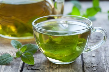 Fresh natural green peppermint tea with peppermint oil in glass cup